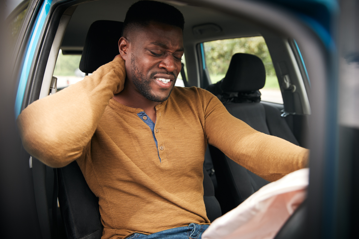 A man is grabbing his neck after being hit by an airbag deployed in a car crash, Airbags can cause injuries in car accidents say Boston injury lawyer