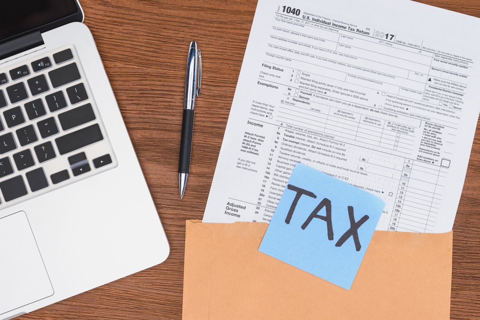 Tax filings sit out on a table next to a computer in a Massachusetts home. A Boston injury lawyer explains that you don't need to claim injury settlements as income.