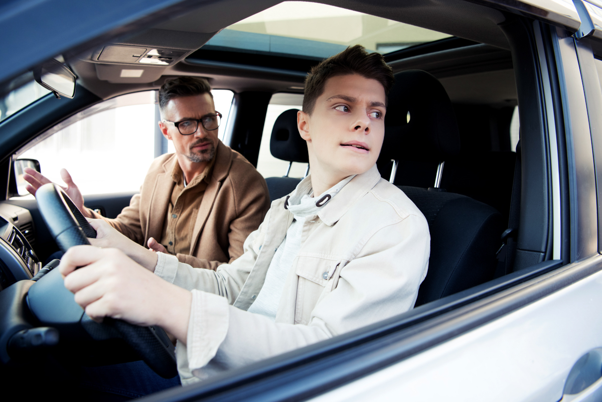 father and son are driving in downtown Boston when the son checks his blindspot to avoid a car accident