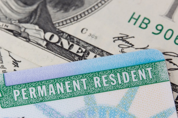 Green card in front of a one hundred dollar bill