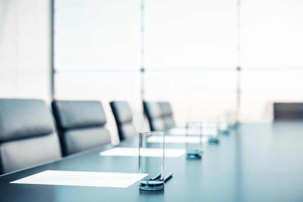 Corporate Boardroom Table With Paper and Water Glasses to Denote the Corporate Transparency Act (CTA)
