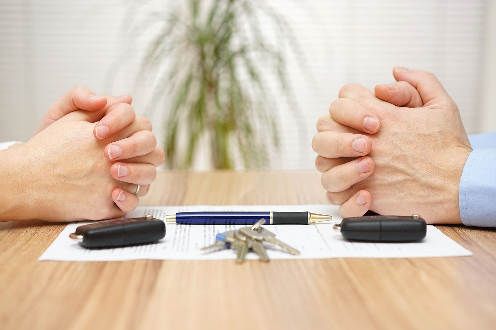 Hands on opposite sides of a negotiation table, divorce settlement in the middle.