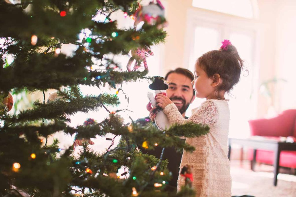 New Mexico parent helps child add ornament to holiday tree.