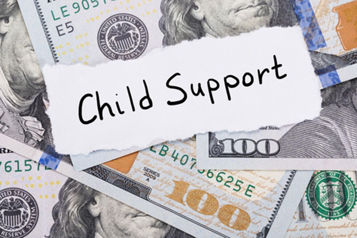 """The words """"Child Support"""" written on a paper which lies on top of hundred dollar bills."""