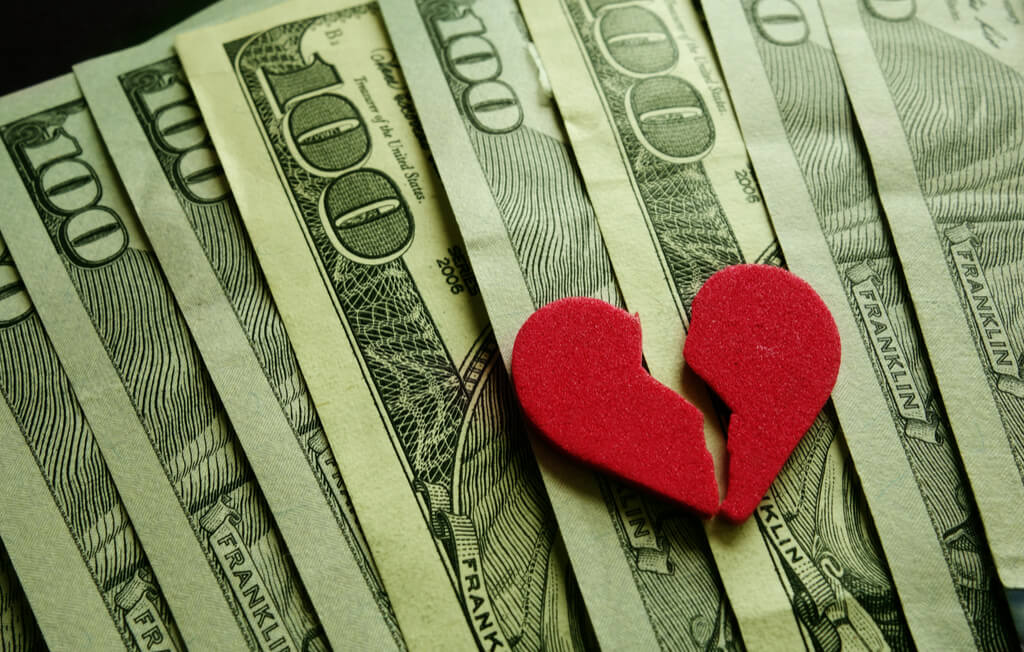 Several hundred dollar bills with a broken heart cutout symbolizing a New Mexico Divorce.