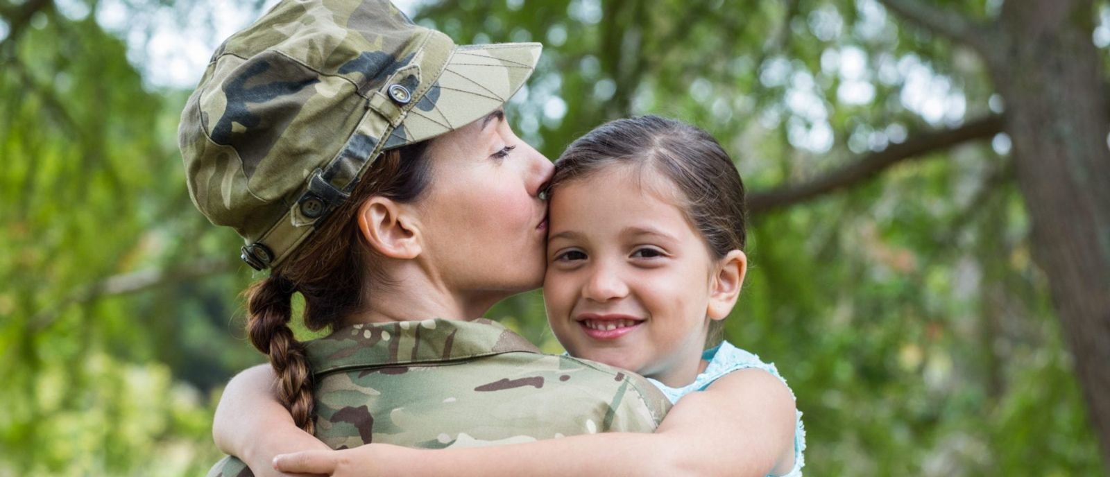 New Mexico military woman kissing daughter on the cheek.
