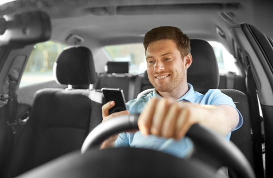 driver using cell phone behind the wheel