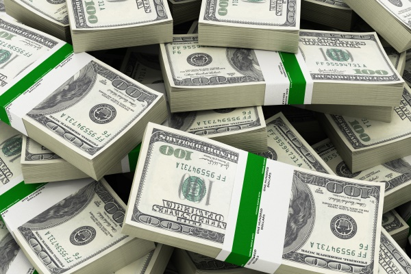 Stacks of hundred dollar bills that are saved with international estate planning
