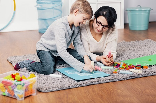 Mother playing on the floor with autistic young boy