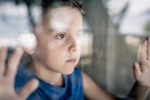 sad boy looking out window