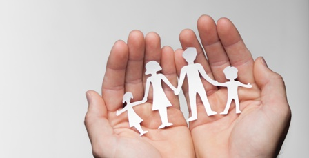 Hands Holding Paper Cut Outs of a Family