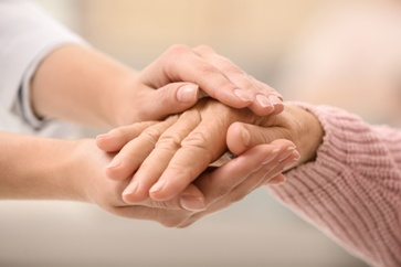 Caregiver Holding an Elderly Patients Hands