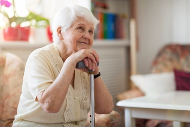Elderly Mother Smiling While Sitting in Her Own House