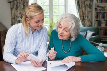 Elderly Woman Signing Power of Attorney Documents