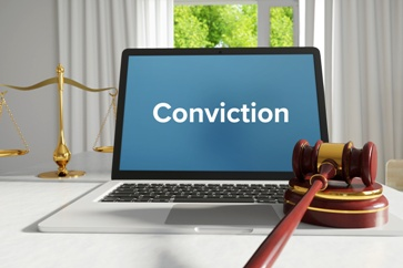 Conviction Text on a Computer Screen With a Gavel and Scales of Justice