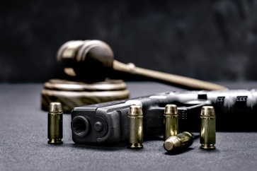 Handgun and Ammo With a Judge's Gavel