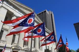 Ohio flags waving in front of the Statehouse in Columbus