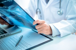 doctor looking at xray of delayed car accident injuries