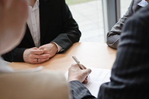 people signing forms around a table
