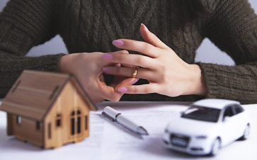 Woman Holding Her Wedding Ring While Looking at Divorce Assets