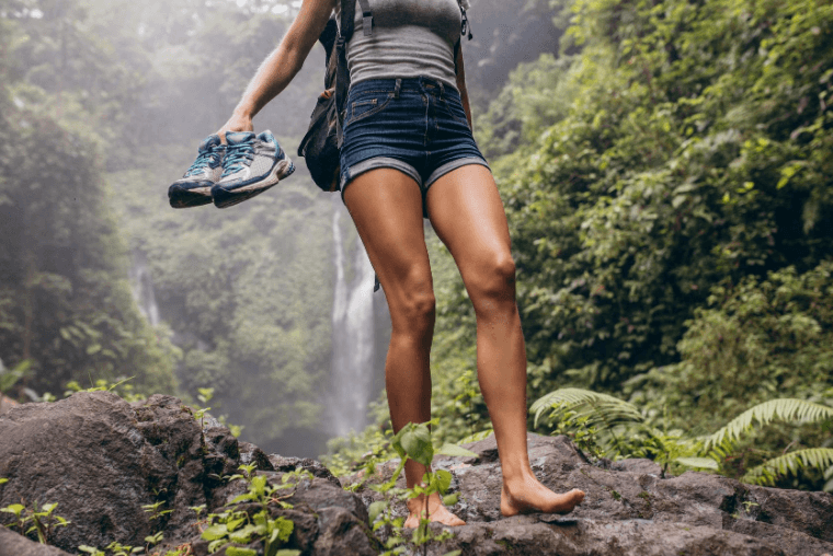 young woman hiking barefoot