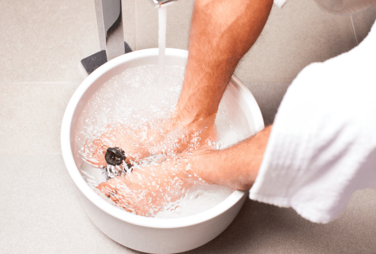 Person soaking their feet in bucket of water