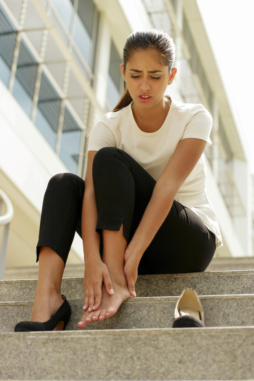 young women sitting on step with painful foot