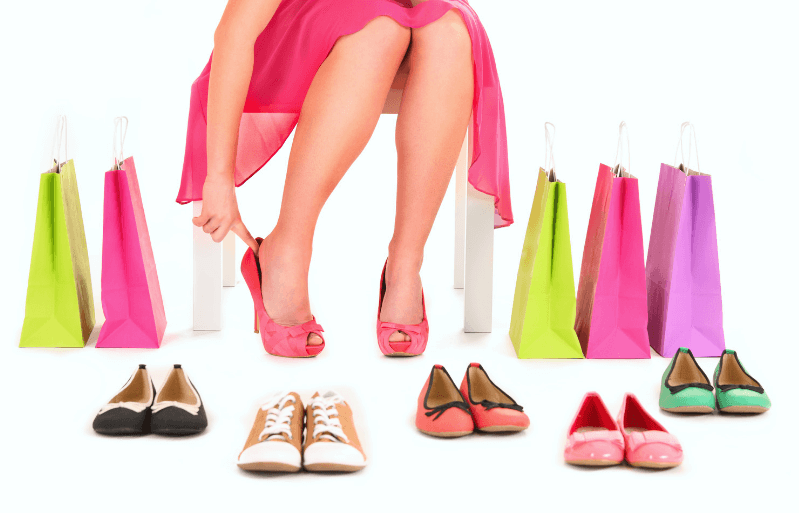 a women trying on multiple pair of shoes