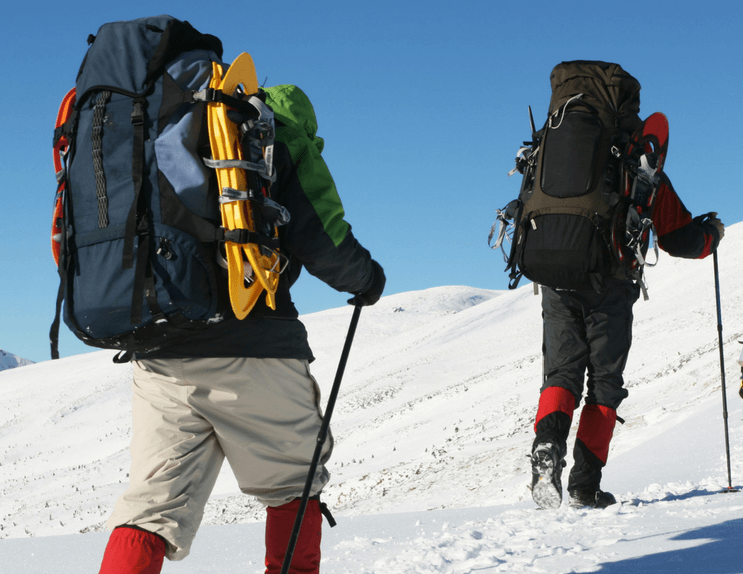 couple hiking on show with backpacks