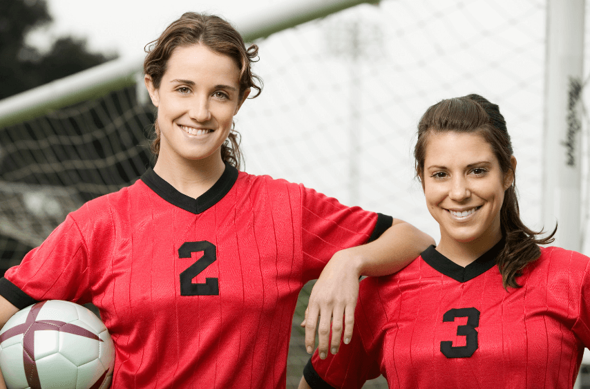 two young women holding a soccer ball