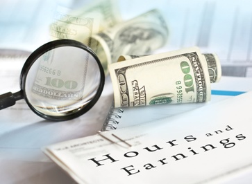 Hours and Earnings Paperwork With Money and a Magnifying Glass
