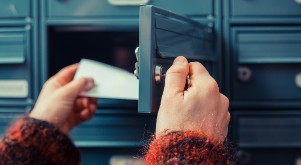 woman getting mail from her mailbox