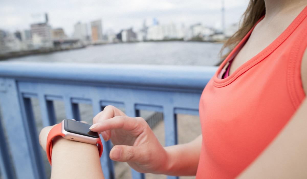 Woman checking time on smart watch during run