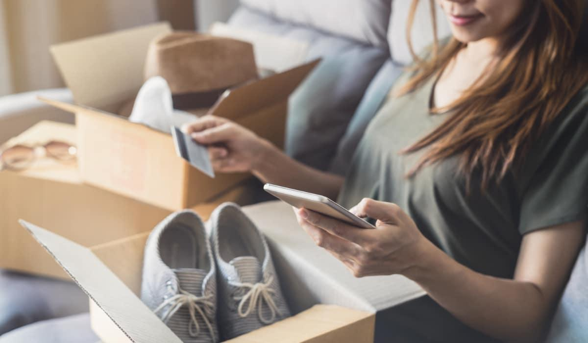 young woman received online shopping opening shoe box