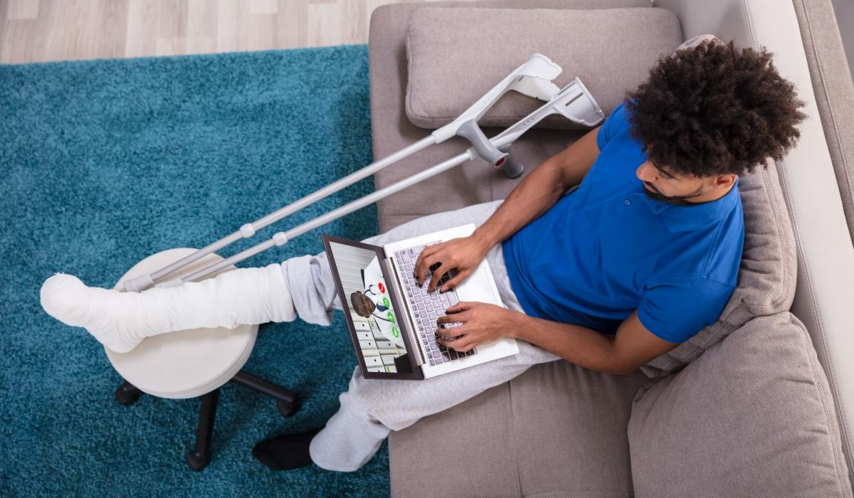 Man video chatting with doctor through laptop
