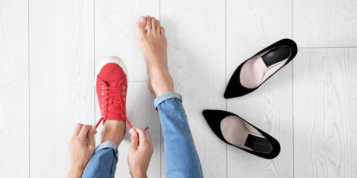 Young woman changing in to tennis shoes on wooden background