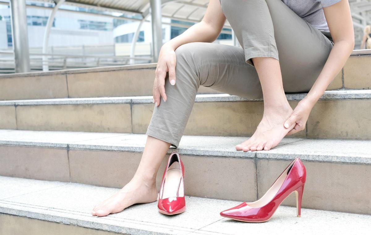 Woman sitting on steps barefoot rubbing heel pain