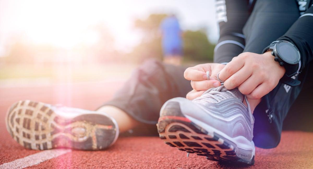 Runner tying shoes sitting down on a track