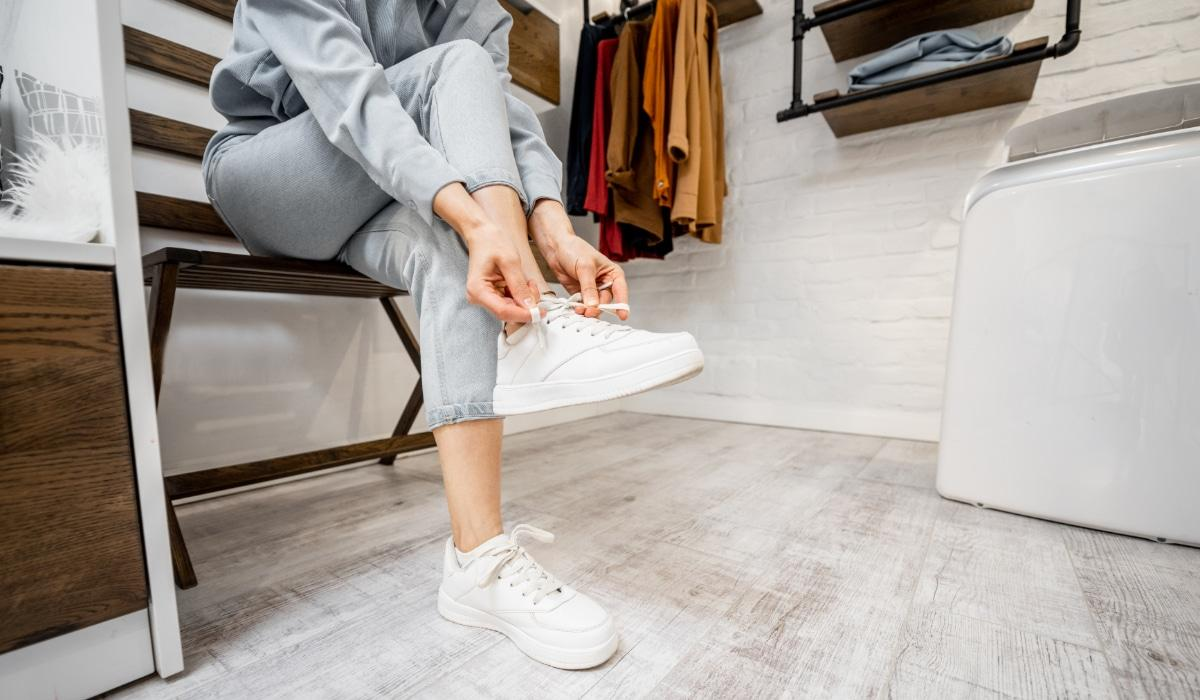 Woman wearing white sneakers in the wardrobe