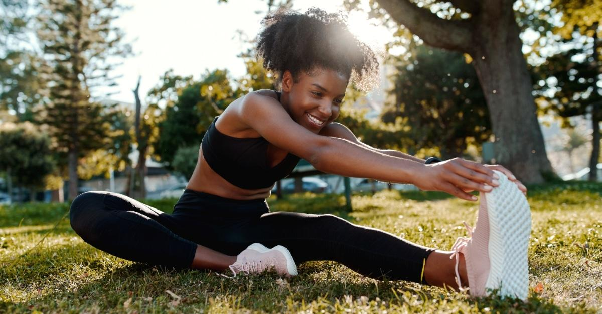Smiling portrait of an sporty fit african american young woman sitting on lawn stretching her legs in the park - happy young black woman warming up her muscles before running