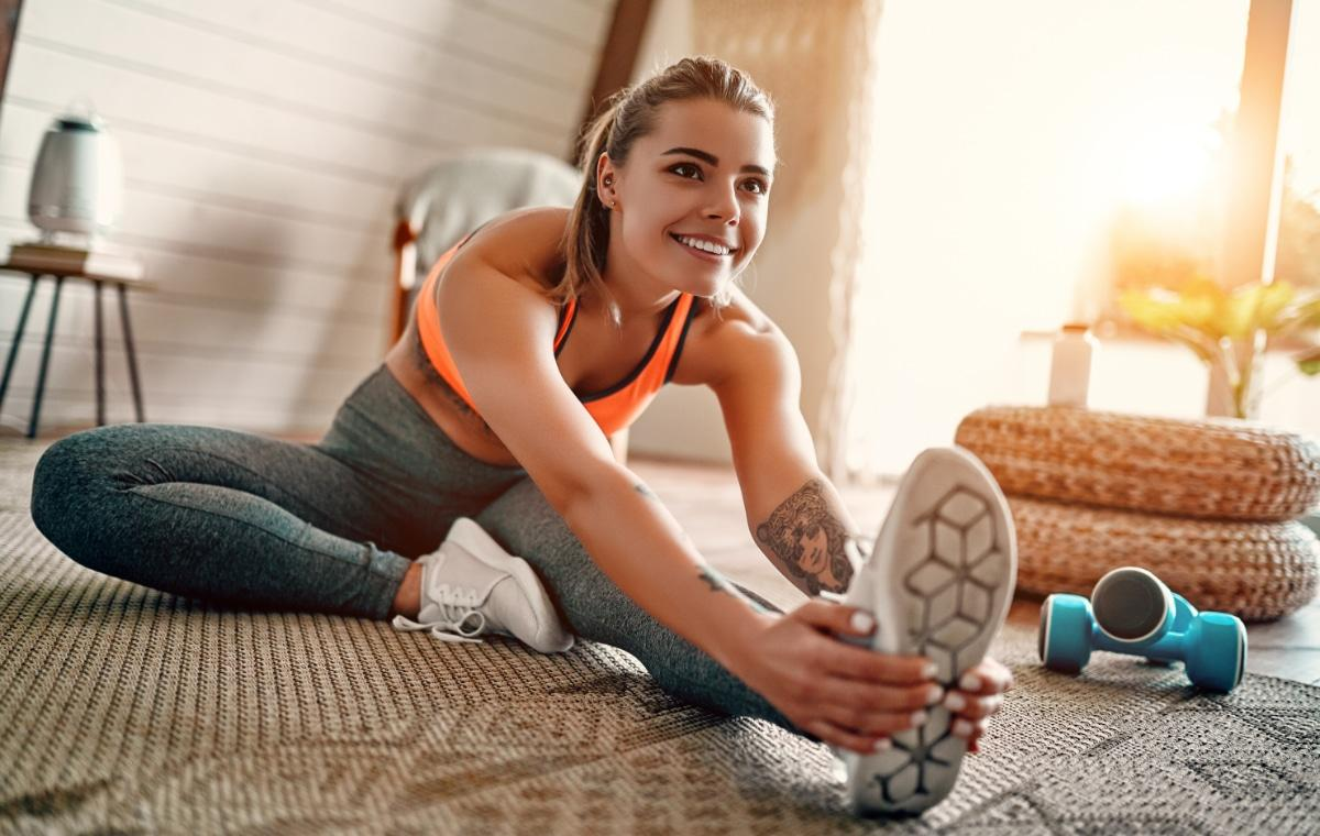 Woman working out in home, stretching on the floor