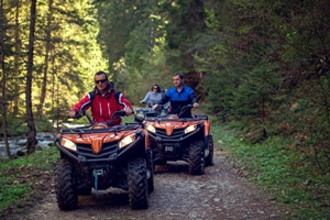 ATV riders on forest trail by river
