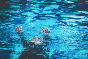child holding hands up as he sinks in a pool Gray and White Law