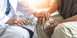 doctor comforting patient by placing his hand on patient's hand