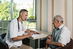 A doctor visits an elderly resident of a nursing home