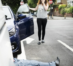 woman getting out of car after hitting pedestrian