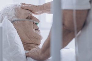 elderly person being checked for fever
