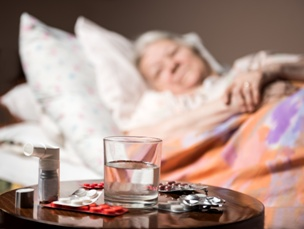 elderly woman in bed looking at table of medication