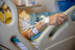 elderly woman in hospital bed nursing home with IV tubes