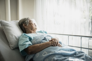 elderly woman in nursing home bed at risk for bedsores